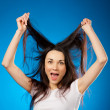 Stock Photo: Funny beautiful brunette girl holding her long hair up