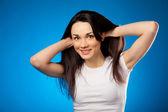 Güzel esmer kız beyaz tişört, mavi backg üzerinde gülümseyen — Stok fotoğraf