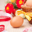 One egg near little basket with ribbons and flowers on wooden ta — Stock Photo