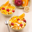 Two bowls with fruit salad on wooden table with spoon — Stock Photo #21373613