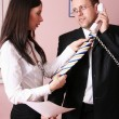 Beautiful secretary helping businessman with his tie — Stock Photo