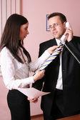 Piękne sekretarz pomaganie biznesmen z jego krawat — Zdjęcie stockowe