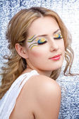 Pretty young woman portrait with bright yellow and blue make-up and long eyelashes — Foto de Stock