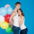 Smiling young love couple holding diversicolored balloons — Stock Photo #22801136