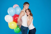 Smiling young love couple holding diversicolored balloons — Stock Photo