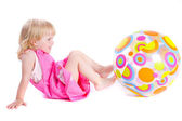 Baby in pink dress playing with coloful ball — Stock Photo
