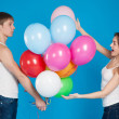 Young boy presenting balloons to a girl. — Stock Photo