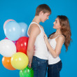 Smiling young love couple holding balloons in the studio — Stock Photo #23066392