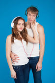 Young love couple. Boy holding girl. wearing headphones, listeni — Stock Photo