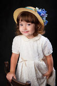 Cute little girl in whte dress and hat with blue flowers — Stock Photo
