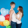 Smiling young love couple holding balloons in the studio — Stock Photo #24020627