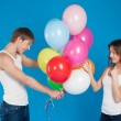 Smiling young love couple holding balloons in the studio — Stock Photo #24020641