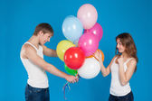 Smiling young love couple holding balloons in the studio — Stock Photo