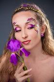 Vacker flicka med ljusa make-up håller lila iris — Stockfoto