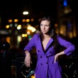 Girl in purple coat oudoor at night  — Stock Photo