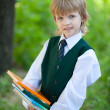 Boy in suit holding books in the park - Stock Photo