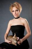 Hermosa joven rubia en vestido negro tenencia gato — Foto de Stock