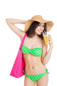 Brunette girl in green swimsuit and hat, holding glass of orange — Stock Photo