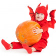 Little boy in red devil costume sitting and holding big pumpkin — Stock Photo #32155991