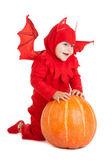 Niño con disfraz de diablo rojo sentado junto a la gran calabaza — Foto de Stock