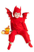 Little boy in red devil costume sitting with pumpkins — Stock Photo