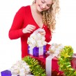 Beautiful blonde curly smiling girl with present — Stock Photo