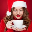 Brunette girl in Santa Clause hat holding white mug — Stock Photo