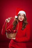 Beautiful girl holding basket with christmas tree decorations — Stock Photo