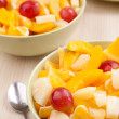 Two bowls with fruit salad on wooden table with spoon — Stock Photo #34831613