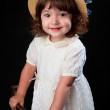 Cute little girl in white dress and hat with blue flowers — Stock Photo