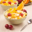 Two bowls with fruit salad on wooden table with spoon — Stock Photo #34832901
