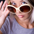 Blonde young woman holding sun-glasses in studio — Stock Photo