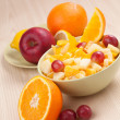 Two bowls with fruit salad on wooden table with half of orange  — Stock Photo
