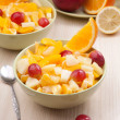 Two bowls with fruit salad on wooden table with spoon — Stock Photo #34833345