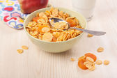 Green bowl of crunchy corn flakes for breakfast with apple on wo — Stock Photo