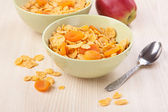 Green bowls of crunchy corn flakes for breakfast with apple — Stock Photo