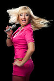 Singer in pink clothes holding microphone — Stock Photo