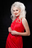 Studio shot of a young, beautiful, blonde woman in red dress — Stock Photo