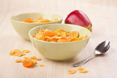 Green bowls of crunchy corn flakes for breakfast with apple on w — Stock Photo