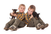 Smiling boys holding puppies lie on the floor — Fotografia Stock
