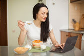 Girl having breakfast and using her laptop in the kitchen — Stock Photo