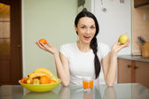 Brunette girl holding fruits sitting in the kitchen — Stock Photo