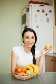 Brunette girl holding fruits sitting in the kitchen  — Stok fotoğraf