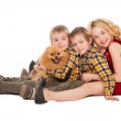 Three children playing with little dog sitting on white backgrou — Stock Photo #47317365