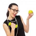 Brunette businesswoman in black dress holding apple and dumbbell — Stock Photo