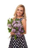 Blonde smiling girl in dot dress holding flower — Stock Photo