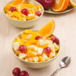 Two bowls with fruit salad on wooden table with spoon — Stock Photo #47868709