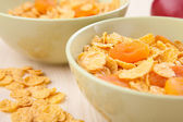 Green bowls of crunchy corn flakes for breakfast on wooden table — Stock Photo