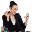 Brunette businesswoman putting on her make-up at work — Stock Photo #50018699