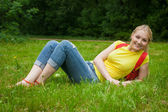 Blonde girl out in the open air wearing jeans and bag — Stock Photo